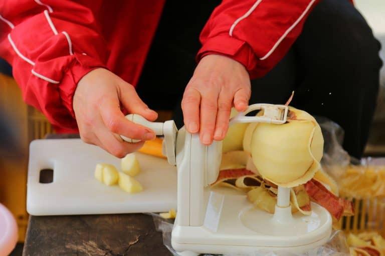 Frau schält Apfel mit Apfelschäler