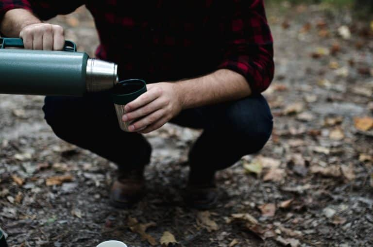 Mann schenkt aus Thermoskanne aus